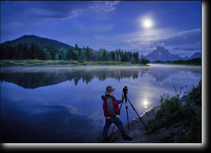 Daryl L.Hunter photographing a setting moon in Grand Teton National Park at Oxbow Bend